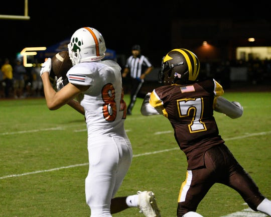 Porterville's Brian Lemus hauls in a touchdown reception against a Golden West defender in a non-league high school football game at Visalia Community Stadium on Friday, Sept. 20, 2019.