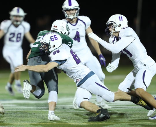 John Jay-Cross River Gavin Fiacco (66) puts a tackle on Brewster's Thomas Consolato (23) during their 34-14 win at Brewster High School on Friday, September 20, 2019.