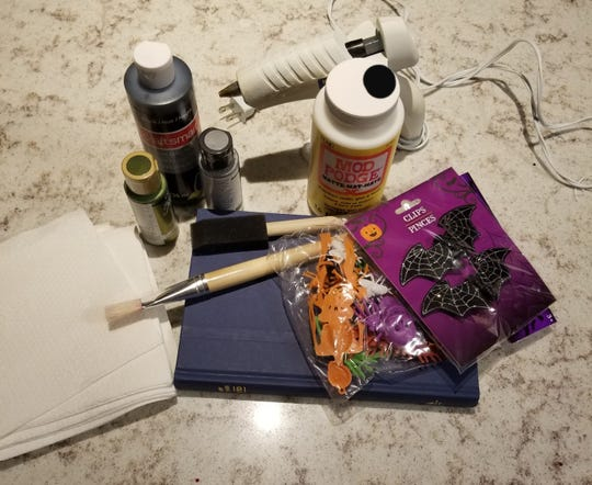 Materials needed to make your own potions/spells book for Halloween decorations include: an old book, glue gun, cheap, plain, white napkins, decoupage glue, such as Mod Podge, various size paint brushes.