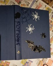 To make a potion/spell book for Halloween decorations, remove the dust jacket off the book and recycle it. Make sure the book is clean and dust free. On the front cover, use the glue gun and create a simple spider web, skull or other spooky shapes.