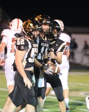 Dylan Briggs (left), Justin Browning (middle), and Daniel DeLaRosa (right) celebrate after Archer City succeeds in an onside kick.