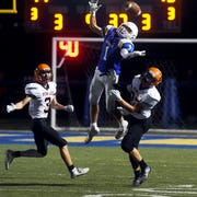 Mason Swauger tries to haul in a pass over C.J. Ratliff during the second half of Maysville's 21-13 win against visiting New Lexington on Friday night in Newton Township.