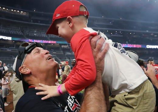 September 20: Braves manager Brian Snitker raises his grandson Luke as he celebrates the decisive victory against the Giants.