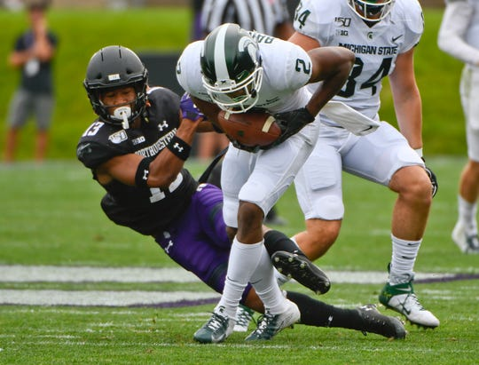 Northwestern Wildcats defensive back JR Pace (13) tackles Michigan State Spartans wide receiver Julian Barnett (2) during the second half at Ryan Field.