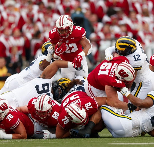 Wisconsin running back Jonathan Taylor leaps over the Michigan defense for a first down during the first quarter at Camp Randall Stadium.