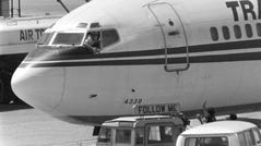 In this Wednesday, June 19, 1985 file photo, a hijacker points a weapon toward an ABC news media crew from the window of the cockpit of the TWA jet as the television crew approaches the jet for an interview at Beirut International Airport, Lebanon.