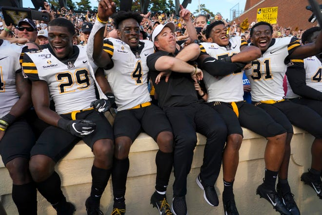Appalachian State Mountaineers head coach Eliah Drinkwitz and his players celebrate after defeating the North Carolina Tar Heels at Kenan Memorial Stadium.