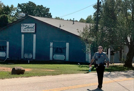 A Lancaster County Sheriff's deputy walks around the Old Skool Sports Bar and Grill, the scene of a shooting early in the morning, north of Lancaster, S.C. on Sept. 21, 2019.  Lancaster County Sherriff's Office said in a statement that the agency was investigating a fatal shooting that also injured several people.