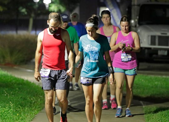 Runners walk back to their vehicles after the Community First Fox Cities Marathon Presented by Miron Construction was cancelled Sunday due to weather.