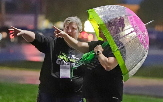 Katrina Gamico of Community First Credit Union, left, gives directions to a runner following the cancellation of the Fox Cities Marathon on Sunday.