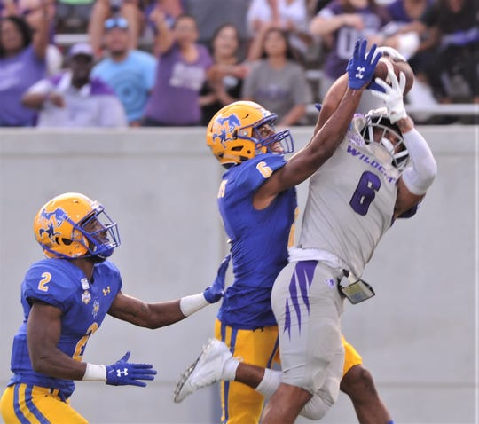 ACU receiver Justus Lee, right, makes a catch while McNeese's Calum Foster and Cade Bartlett (2) defend. It went for a 39-yard catch to the McNeese 8-yard line. ACU ended up getting a field goal out of the drive during the first quarter of the Southland Conference game Saturday, Sept. 21, 2019, at Wildcat Stadium.