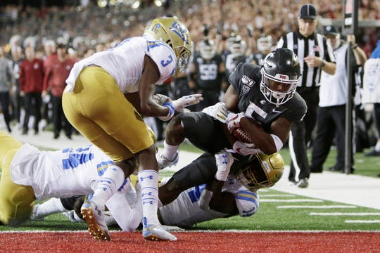 Washington State wide receiver Travell Harris, right, scores a touchdown as he is brought down by UCLA linebacker Krys Barnes, second from right, and defensive back Jay Shaw, left, in front of Rayshad Williams during the first half of an NCAA college football game in Pullman, Wash., Saturday, Sept. 21, 2019.