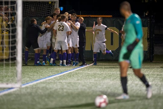 Vermont players celebrate a late goal by Rasmus Tobinski in their 3-0 win over Merrimack at Virtue Field on Saturday night, Sept. 21, 2019.
