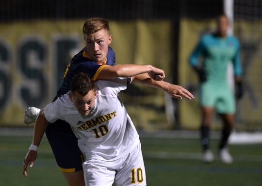 Vermont's Jon Arnar Barddal (10) absorbs the landing of a Merrimack defender during a college men's soccer game at Virtue Field on Saturday night, Sept. 21, 2019.