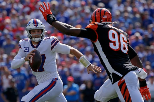 Buffalo Bills quarterback Josh Allen (17) runs from Cincinnati Bengals defensive end Carlos Dunlap (96) in the first quarter of the NFL Week 3 game between the Buffalo Bills and the Cincinnati Bengals at New Era Stadium in Buffalo, N.Y., on Sunday, Sept. 22, 2019. The Bills led 14-0 at halftime.