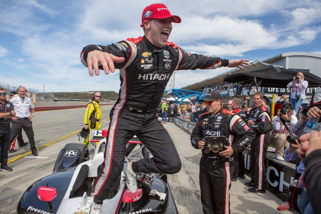 Josef Newgarden jumps from his car to celebrate with his team after winning the championship at Laguna Seca Raceway in Monterey, Calif., on Sunday.
