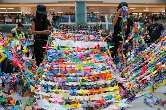 Protesters arranging origami cranes used in a display at an anti-government rally inside a shopping mall at the Sha Tin district on Sunday.