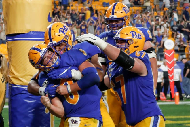Pittsburgh quarterback Kenny Pickett (8) celebrates with teammates after he caught a pass for a touchdown against Central Florida during the second half on Saturday.
