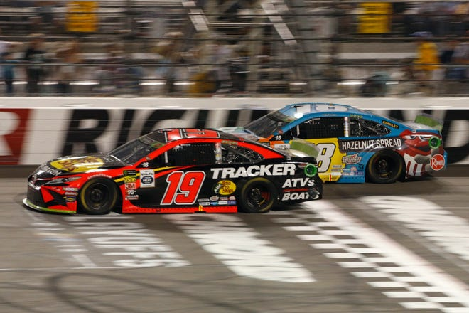 Martin Truex Jr. (19) passes Kyle Busch (18) during the Cup Series race at Richmond.
