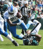 The Lions' Kerryon Johnson breaks away from the Eagles' Brandon Graham on a run in the second quarter.