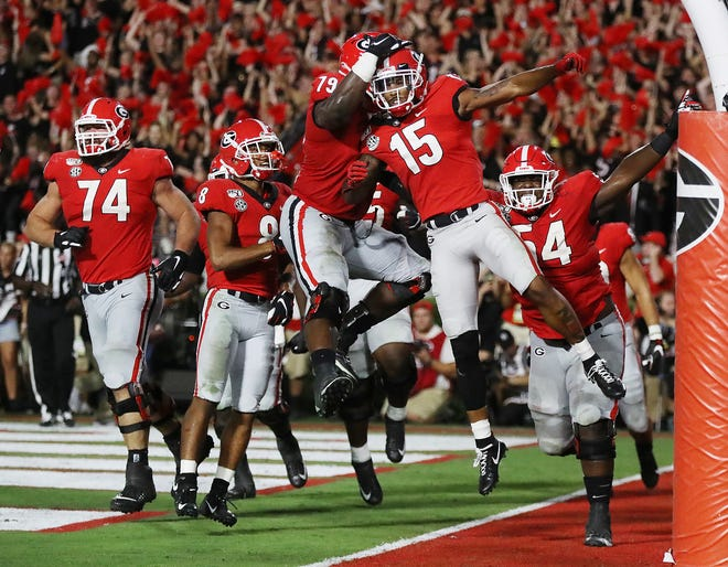 Georgia wide receiver Lawrence Cager (15) celebrates his 15-yard touchdown catch with Makiya Tongue and teammates during the fourth quarter.