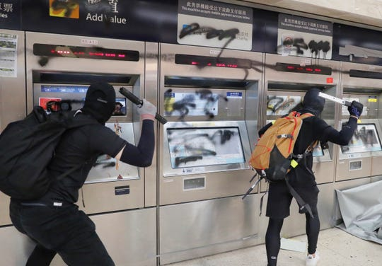 Protesters vandalize a subway station Sunday, in Hong Kong. Protesters smashed surveillance cameras and electronic ticket sensors in the subway station, as pro-democracy demonstrations took a violent turn once again.