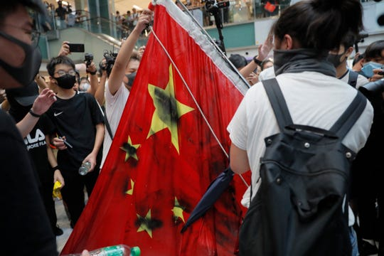 Protesters vandalize a Chinese national flag during a protest at a mall in Hong Kong on Sunday.