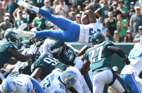 Lions' Kerryon Johnson goes over the top for a touchdown in the second quarter against the Eagles.