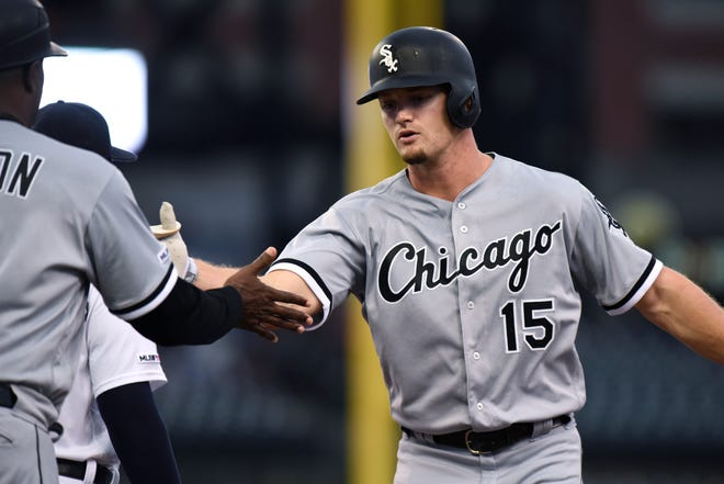 Chicago White Sox's Adam Engel, right, hits a single and is congratulated by first base coach Daryl Boston during the third inning.