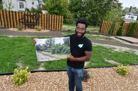 Daniel A. Washington holds a before photo of the area, and now stands in the new created park.