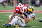Michigan quarterback Dylan McCaffrey is tackled by Wisconsin safety Eric Burrell in the third quarter.  Burrell was given a targeting penalty on the play and was ejected from the game.