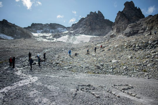 The letters 'RIP' (rest in peace) are written with stones during a commemoration in front of the 'dying' glacier of Pizol mountain in Wangs, Switzerland, Sunday. Various organizations gathered to shine a light on climate change and melting glaciers.