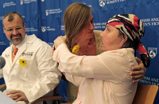 Carmen Blandin Tarleton of Thetford, Vermont, right, is embraced by Marinda Righter, daughter of face donor Cheryl Denelli-Righter, at Brigham and Women's Hospital in Boston, Mass., Wednesday, May 1, 2013. At left is her surgeon, Dr. Bohdan Pomahac.