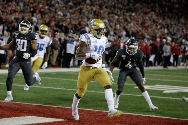 UCLA wide receiver Demetric Felton  scores the go-ahead touchdown during the second half.