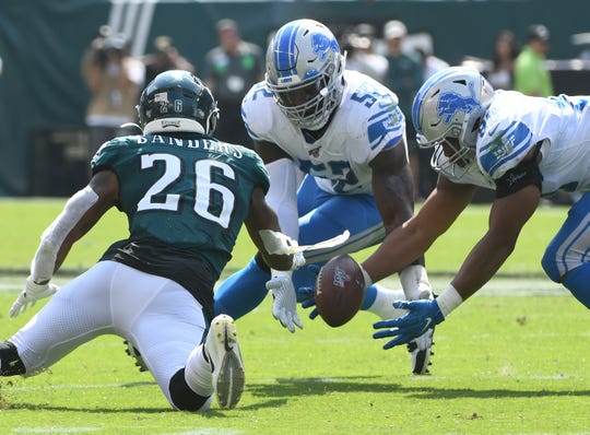 Eagles' Miles Sanders loses the ball with Lions' Christian Jones and Trey Flowers diving in. The Eagles were able to recover and maintain possession in the second quarter.