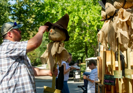 Chris Woods of Wadesville adjusts the hat on one of the handmade scarecrows he is selling at Kunstfest in New Harmony, Ind., Saturday afternoon, Sept. 21, 2019.