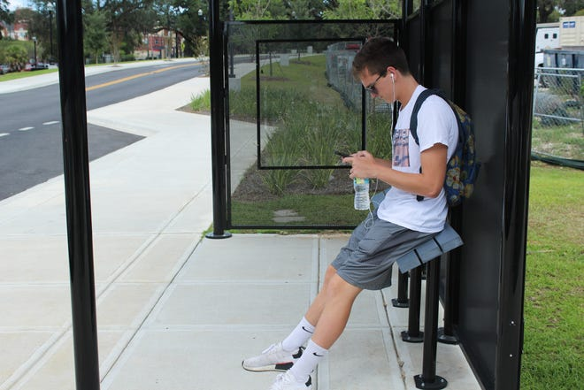 A student leans against the perch bench located on Chieftan Way on the Renegade bus route.