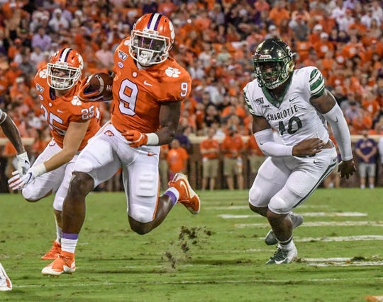 Clemson running back Travis Etienne (9) runs near Charlotte linebacker Markees Watts(40) during the first quarter at Memorial Stadium in Clemson, South Carolina Saturday, September 21, 2019.