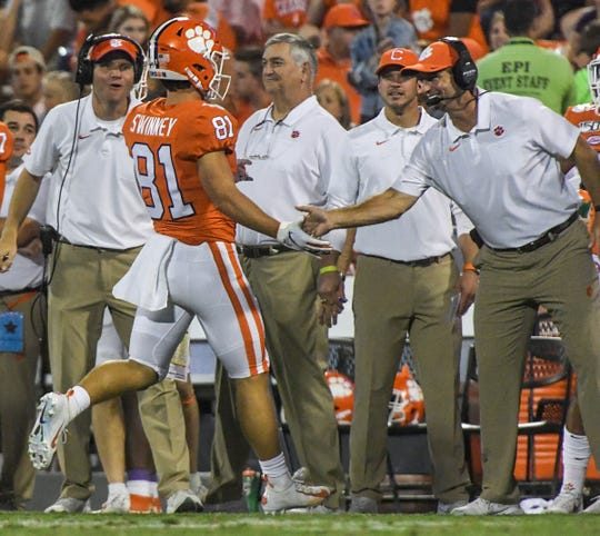 Clemson wide receiver Drew Swinney (81) runs back to the sidelines and is greeted by his father Clemson Head Coach Dabo Swinney after a catch against Charlotte during the fourth quarter at Memorial Stadium in Clemson, South Carolina Saturday, September 21, 2019.