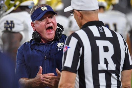Notre Dame Fighting Irish head coach Brian Kelly talks to the officials after a penalty on a punt play against the Georgia Bulldogs during the second half at Sanford Stadium.