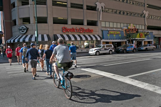 Indianapolis Colts and Atlanta Falcons fans head to Lucas Oil Stadium on Sunday, Sept. 22, 2019, crossing Maryland Street at Illinois Street, near where six people were shot the night before.