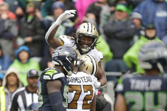 New Orleans Saints' Alvin Kamara, top, celebrates his touchdown against the Seattle Seahawks during the first half of an NFL football game, Sunday, Sept. 22, 2019, in Seattle. (AP Photo/Scott Eklund)