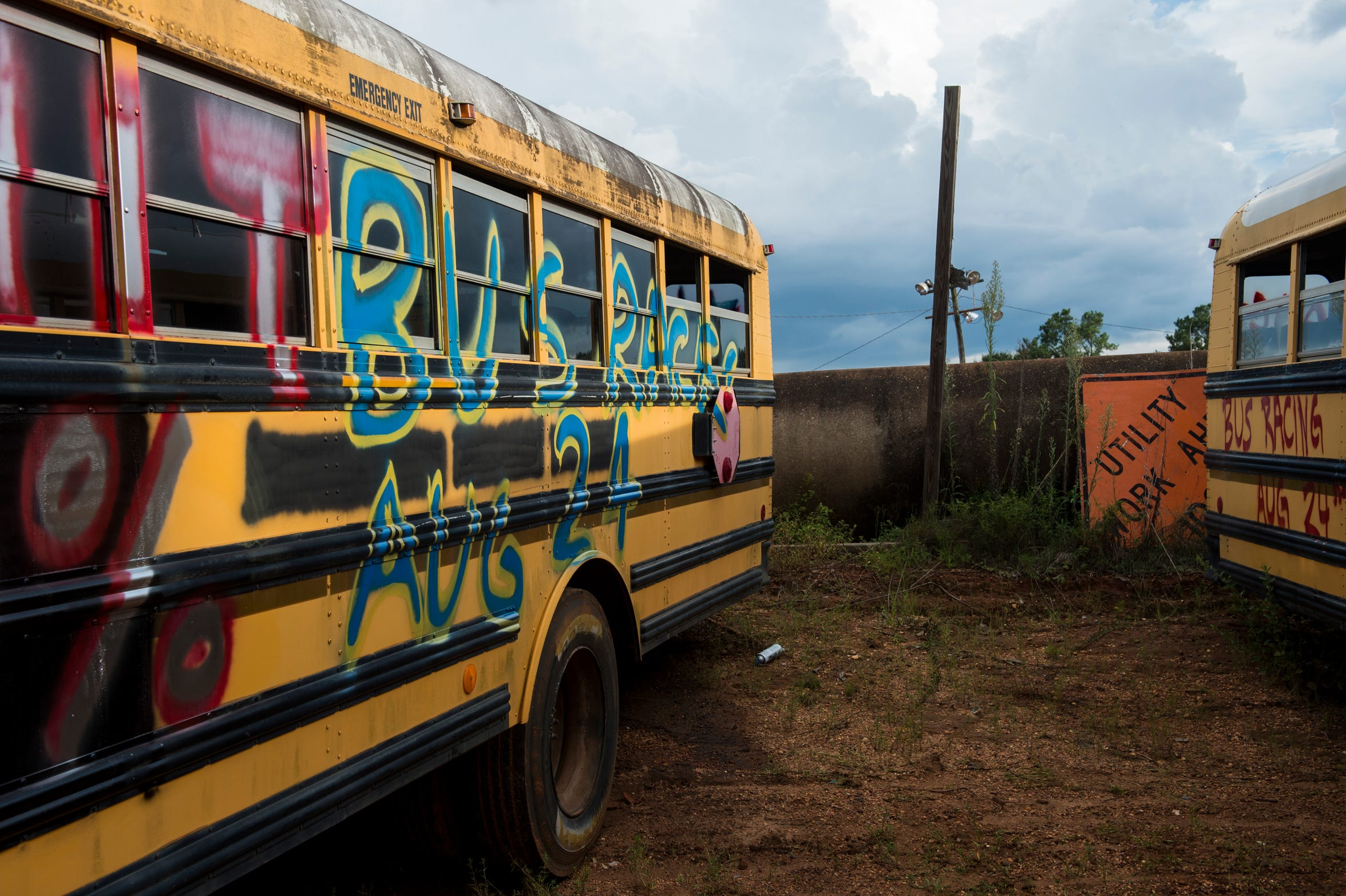School buses are spray painted by each driver before the race at Flomaton Speedway in Flomaton, Ala., on Saturday, Aug. 24, 2019.