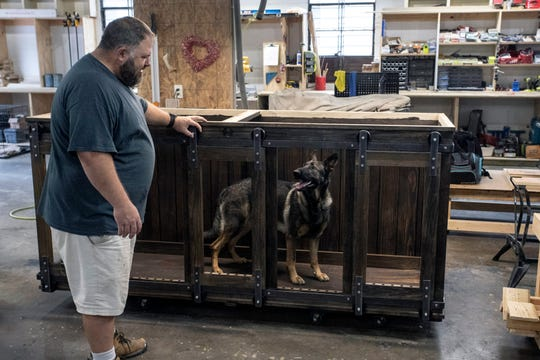 Roy Mills' German shepherd Samantha takes a closer look at one of the custom doghouses being built at Kentucky Barnwood Kennels.