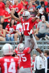 Ohio State tackle Thayer Munford lifts wide receiver Chris Olave in the air after one of his two touchdown catches in Saturday's 76-5 victory over Miami of Ohio.