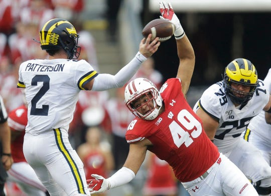 Wisconsin Badgers linebacker Christian Bell (49) rushes Michigan Wolverines quarterback Shea Patterson (2).