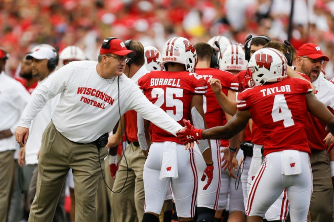 Wisconsin head coach Paul Chryst congratulates wide receiver A.J. Taylor after a Wisconsin touchdown on Saturday.