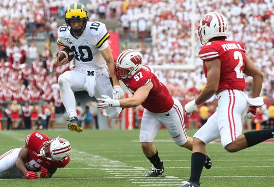 Michigan Wolverines quarterback Dylan McCaffrey (10) runs the ball. McCaffrey suffered a concussion on the play and did not return to the game. The Badgers won the game, 35-14.