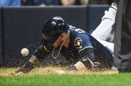 Brewers catcher Yasmani Grandal scores a run in the sixth inning Saturday night at Miller Park.
