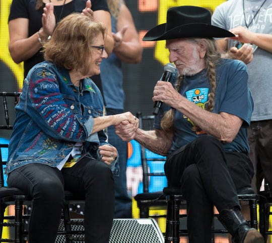 Willie Nelson, right, thanks long-time Farm Aid executive director Carolyn Mugar during a news conference Saturday at Alpine Valley.